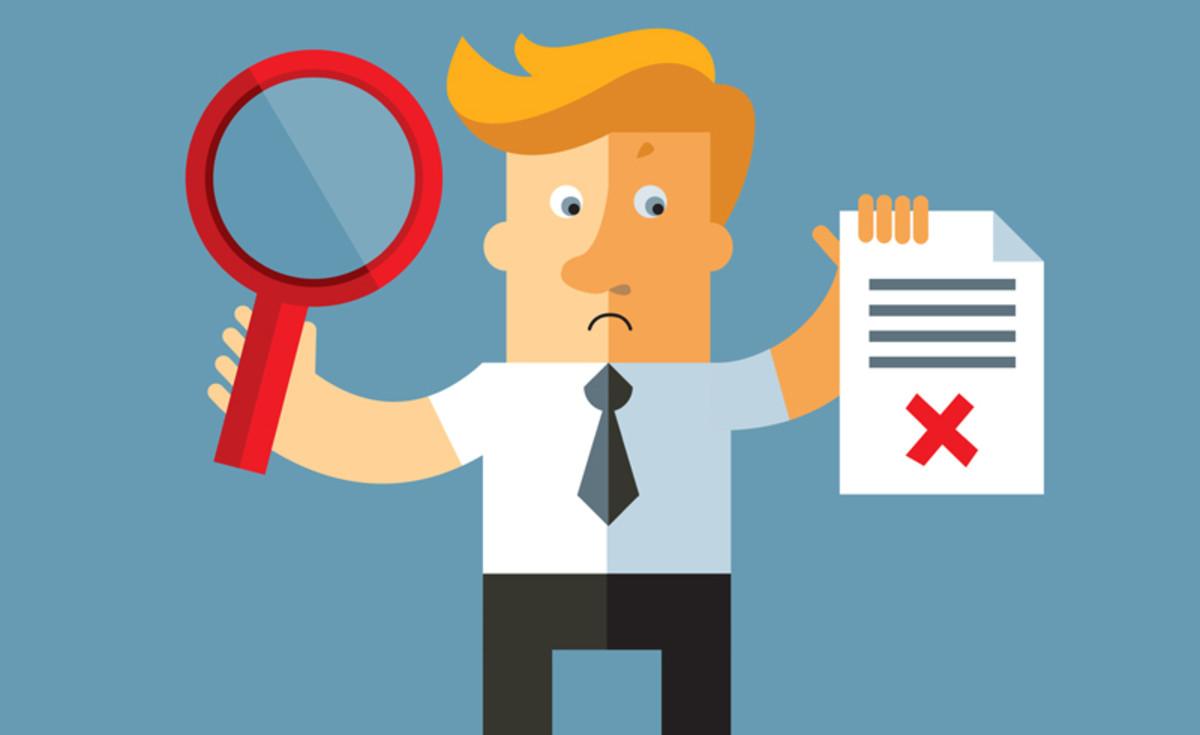 một người đàn ông đang cầm bài kiểm tra và dùng kính lúp tìm lỗi sai - hình ảnh minh họa sai lầm luyện thi tiếng Anh lớp 9