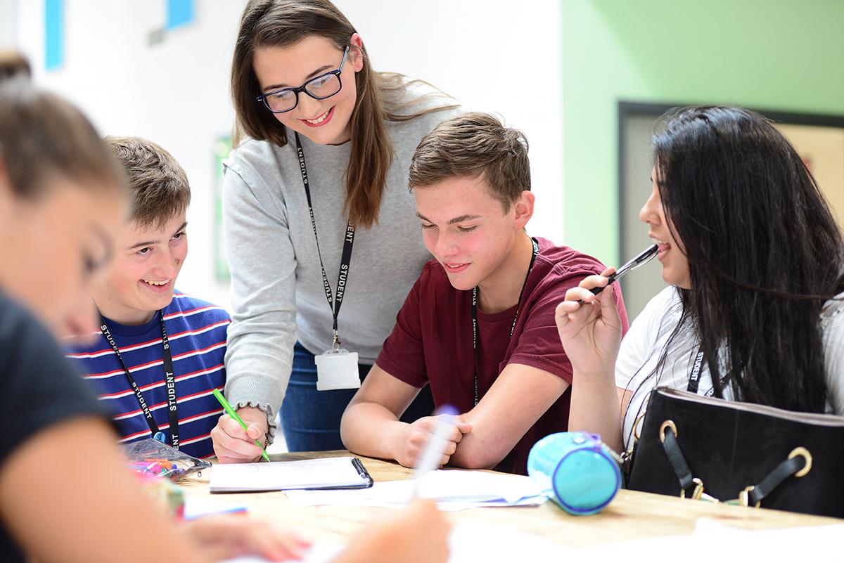 một cô giáo đang hướng dẫn bài cho 4 bạn học sinh
