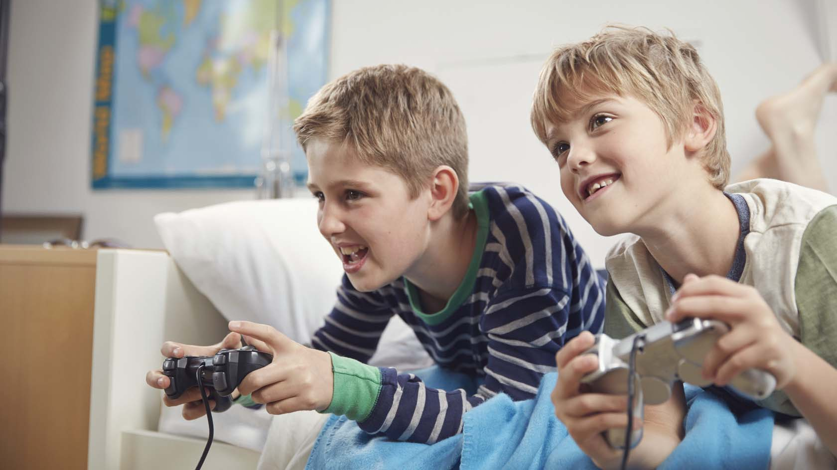 hai cậu bé đnag mải mê chơi điện tử - hình ảnh minh họa cho Ving làm bổ ngữu cho tân ngữ 2