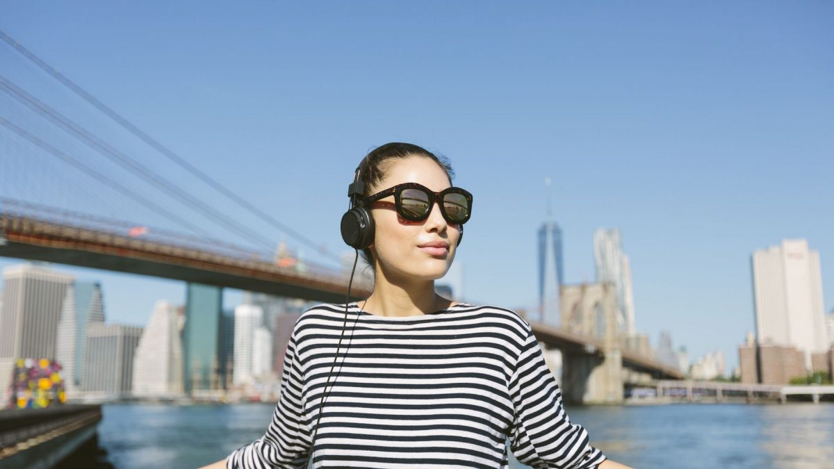 Một cô gái đang đeo tai nghe vừa cập nhật tin tức vừa đứng thư giãn trên cầu
