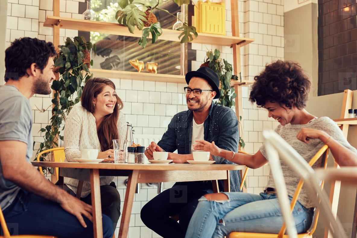 4 người bạn đang vui vẻ nói chuyện với nhau trong một quan cà phê