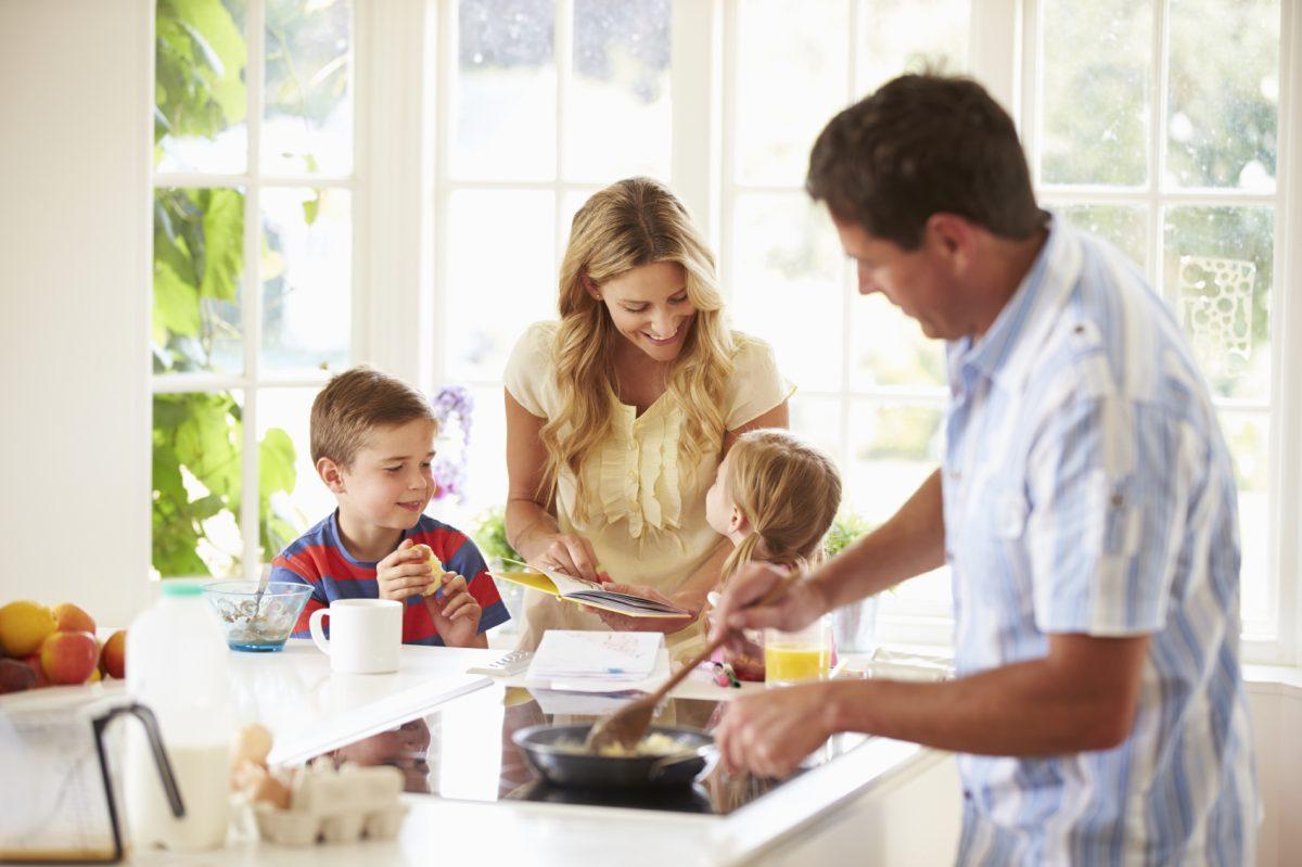 một gia đình có bố và hai con đang cùng nhau nấu ăn