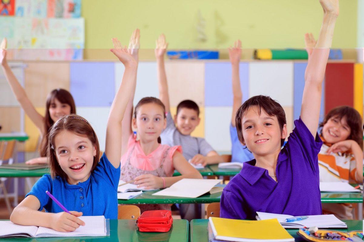 các em học sinh đang ngồi trong lớp giơ tay phát biểu - hình ảnh mình họa cho các từ vựng tiếng Anh lớp 6