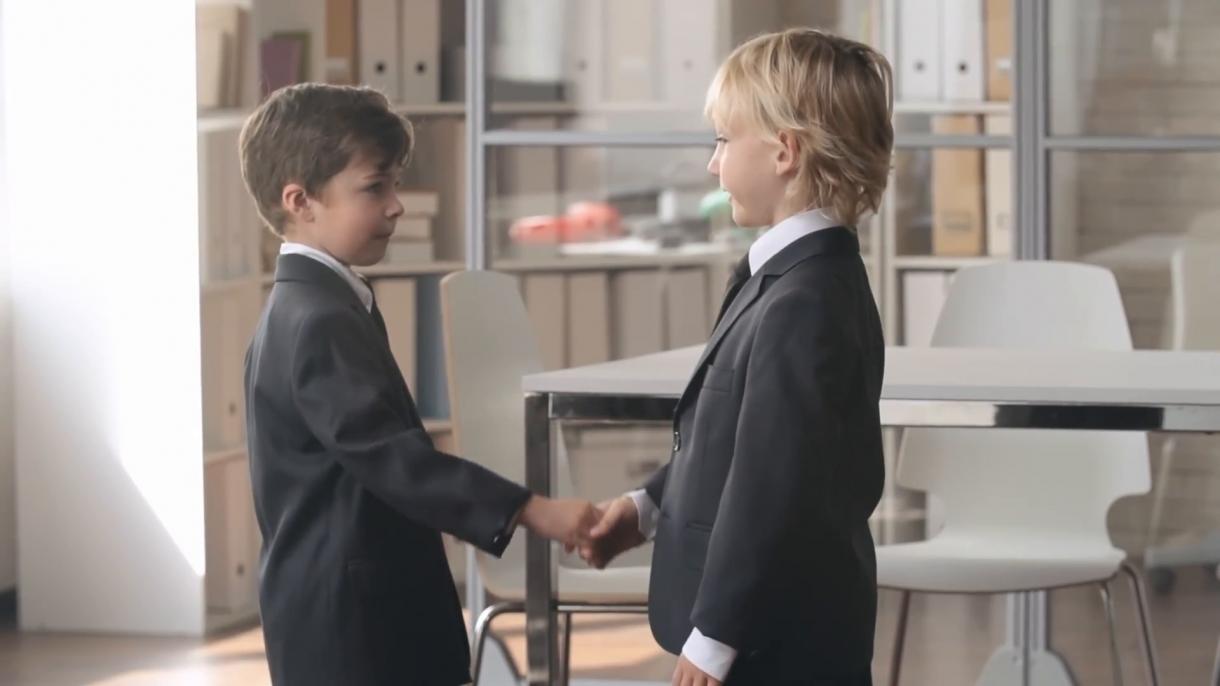 hai cậu bé mặc đồ công sở đang bắt tay chào nhau
