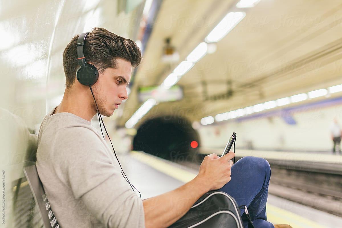 một chàng trai đăng chăm chú luyện nghe bằng điện thoại của mình ở trong mọt ga tàu điện ngầm