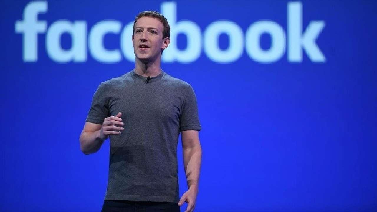 ông chủ Facebook Mark Zuckerberg đang đứng phát biểu, phía sau là hình nền biểu tượng của Facebook