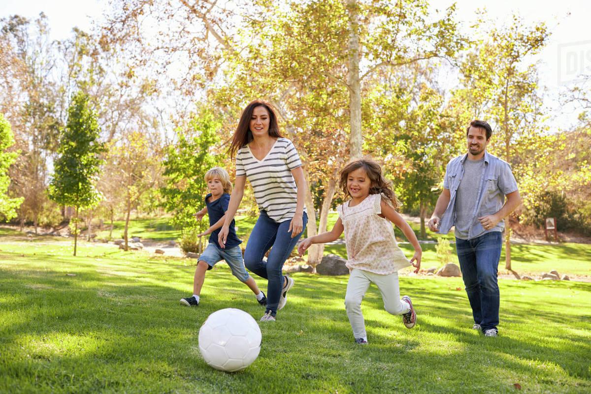 một gia đình đang cùng nhau chơi đá bóng trong công viên - hình ảnh minh họa cho từ vựng tiếng Anh lớp 6