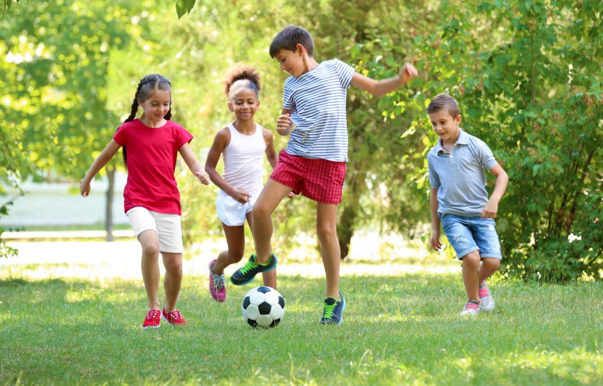 các cô bé cậu bé đang cùng nhau trên bóng đá trong vườn - hình ảnh minh họa cho từ vựng tiếng Anh lớp 3
