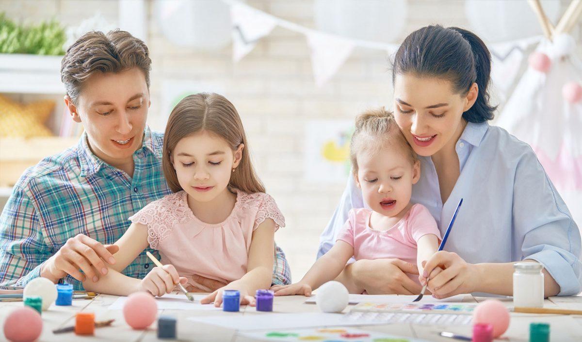 hình ảnh một gia đình có bố đang dạy người chị học bài, mẹ đang chơi với em bé