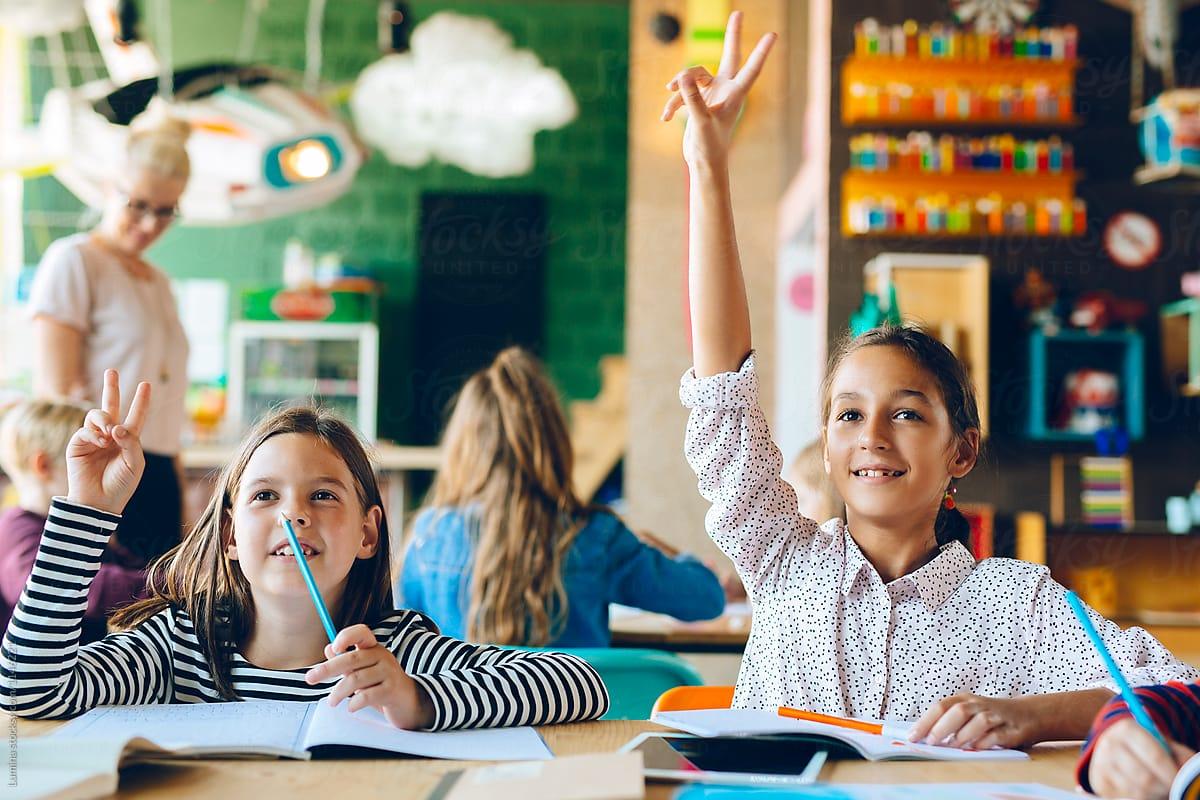 2 bạn học sinh đang giớ tay - hình ảnh minh họa bứt phá tiếng Anh cho học sinh cấp 2